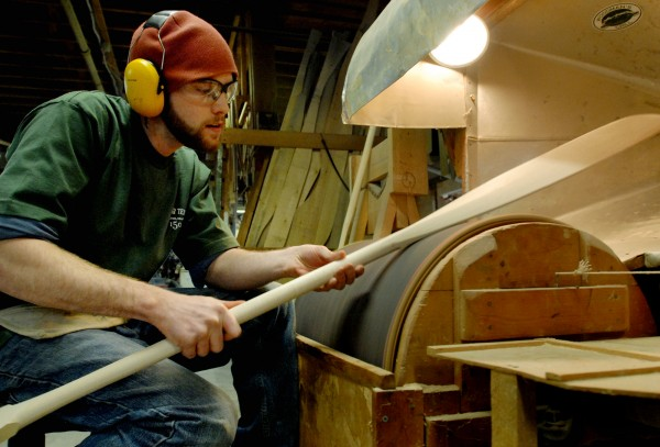 Brandon Viger, employee at Shaw & Tenney in Orono, uses a sanding drum while working on an anniversary paddle for L.L. Bean on Wednesday.