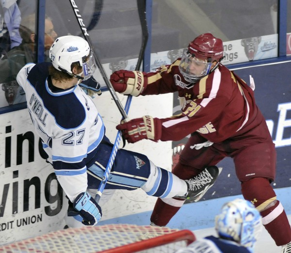 Boston College winger Steven Whitney (21) checks Maine defenseman Will O'Neill (27)  in the first period of their NCAA college hockey game, Friday, Jan. 20, 2012, in Orono, Maine.