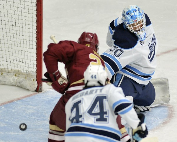 Maine goalie Dan Sullivan (30) fails to stop a shot by Boston College center Bill Arnold (24) in the first period of their NCAA college hockey game, Friday, Jan. 20, 2012, in Orono, Maine.