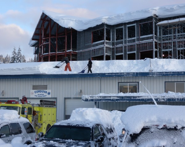 In this Saturday, Jan. 7, 2012 photo provided by the Alaska Division of Homeland Security and Emergency Management, people work to clear snow from the roof of the Cordova volunteer fire department in the fishing town of Cordova, Alaska.