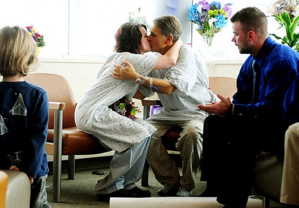 Surrounded by family and friends, Pam LaFreniere, 47, kisses her new husband Barry Hanson, 59, both of Livermore Falls, at Central Maine Medical Center in Lewiston on Tuesday. Their grandson, Reed Anthony, 3, of Boston, is at left, and Reed's uncle, Ian Hanson of Virginia, is at right.