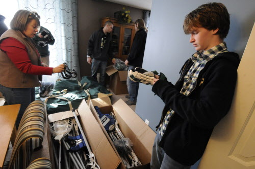 Ezra Frost, 15, a Bangor High School freshman, looks over a glove and some of the other male and female lacrosse equipment that was donated to the Eastern Maine Youth Lacrosse program. On the left is Gayle Middleton, president of Eastern Maine Youth Lacrosse, whose Bangor home served as the drop-off site for the equipment Monday, Jan. 16, 2012.