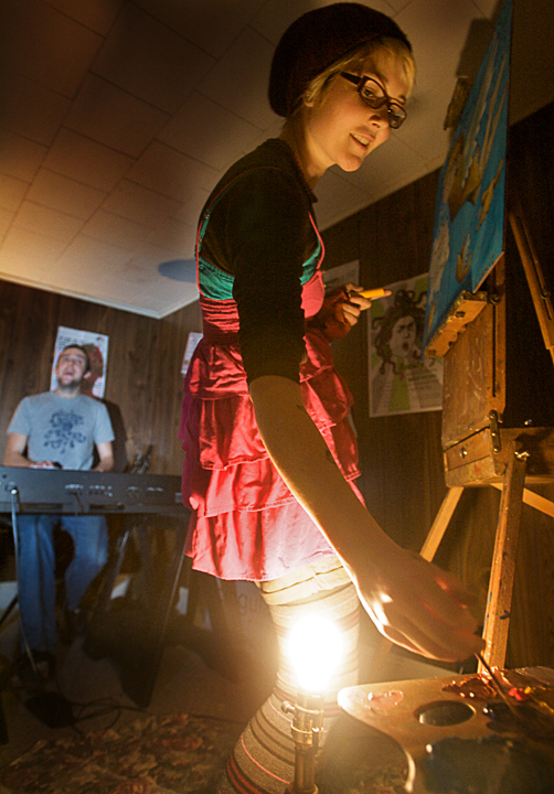 Elizabeth Jancewicz of Pocket Vinyl creates a painting while her husband and partner, Eric Stevenson, sits at the keyboard and sings at a house concert on Jordan Avenue in Brunswick Saturday night. The informal venue, known as The Bombshelter, is booked and operated by resident Nick Dentico.