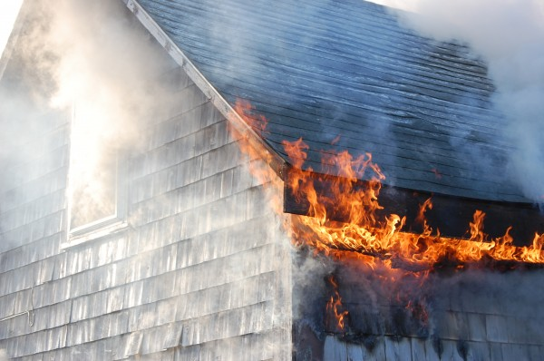 Flames curl around the eaves and smoke pours out a window of this house at 8 Harwood Street in Machias on Monday morning.