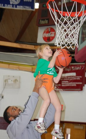 Six-foot-5 Hampton Mack, a University of Maine-Machias varsity basketball player, helps 3-foot-none Kiley Robinson, a 5-year-old Harrington Elementary School studnet, perfect her dunk at Sunday's gathering at Narraguagas High School in Harrington of a community intramural basketball league for K-5 Down East students.