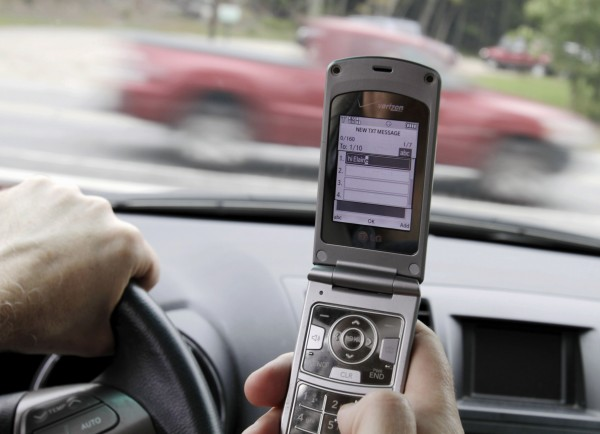 A phone is held in a car in Brunswick in September 2011. Even as drivers are increasingly distracted by cellphones, email and texting, the number of highway deaths dipped to the lowest level in more than five decades in Maine, officials said Sunday.