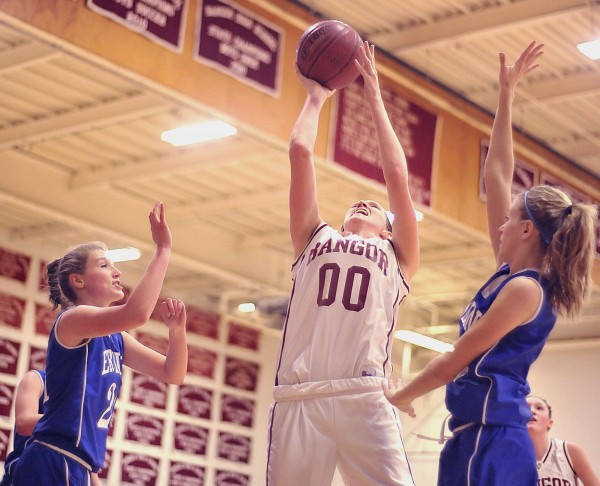 Bangor girl's basketball player Katie Brochu (00) puts up a shot out of reach of Erskine girl's players Amy Phillips (21) and Alyssa Gartley (right) in the first half of their game in Bangor on Friday Jan. 13, 2012.
