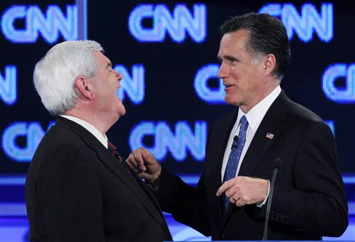 Republican presidential candidates former House Speaker Newt Gingrich and former Massachusetts Gov. Mitt Romney talk during a commercial break at the Republican presidential candidates debate in Jacksonville, Fla., Thursday, Jan. 26, 2012.
