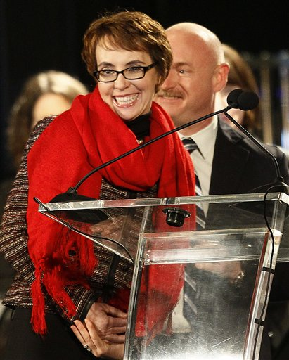 In this Jan. 2, 2012, file photo Rep. Gabrielle Giffords, left, accompanied by her husband, former astronaut Mark Kelly, reacts after leading the Pledge of Allegiance at the start of a memorial vigil remembering the victims and survivors one year after the Arizona congresswoman was wounded in a shooting that killed six othersin Tucson, Ariz. Giffords said Sunday Jan, 22, 2012, that she will resign from Congress this week.