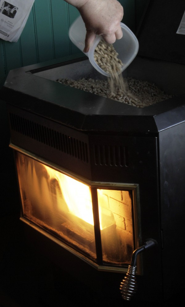 Dan Stevens loads pellets into the pellet stove at his home in Gardiner on Thursday, Jan. 19, 2012. The number of households using wood as a heating source nearly doubled in Maine from 2000 to 2010, while growing by a third nationwide, according to U.S. Census figures.