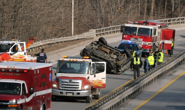 A GMC Envoy SUV is righted after rolling over in the southbound lane of Interstate 95 in Bangor Jan. 3, 2012.