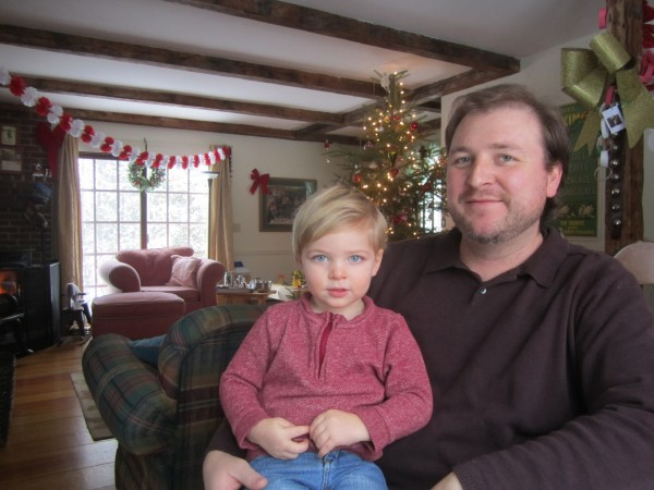 Richard Reinhart, stay-at-home dad, with his son, Henry. Their Christmas tree awaits a belated celebration with out-of-town family.