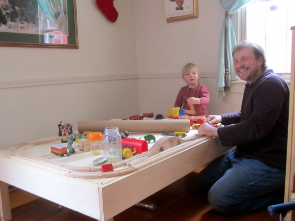 Henry and his dad, Richard Reinhart, play together at the wooden train table that Richard built for Henry's birthday.