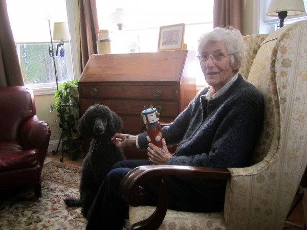 "Janet Ordway, at home with her dog, Cranberry. She is holding a ""Kachina"" that she made out of balsa wood."