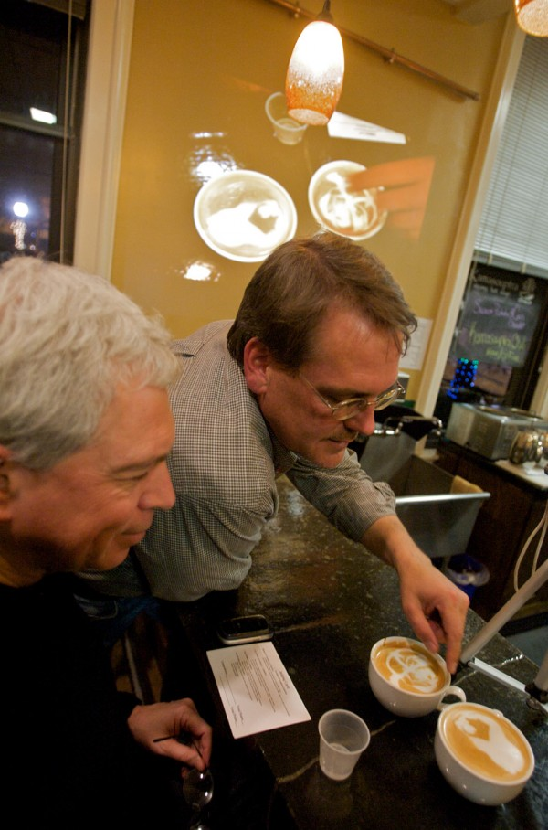 Judges Bud Bernstein, left, and Jeffrey Kingman look over a pair of entries in the Thursday Night Throwdown at Bard Coffee. Points are given for symmetry, color, use of space and the overall impression.