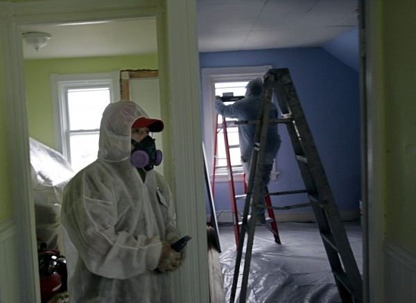 In this Thursday, Feb. 23, 2006 photo, contractors Luis Benitez, foreground, and Jose Diaz, background, clean up lead paint in a contaminated building in Providence, R.I. A federal panel recommended Wednesday that the threshold for lead poisoning in children should be lowered. If adopted by government officials, hundreds of thousands of additional U.S. children could be classified as having lead poisoning.