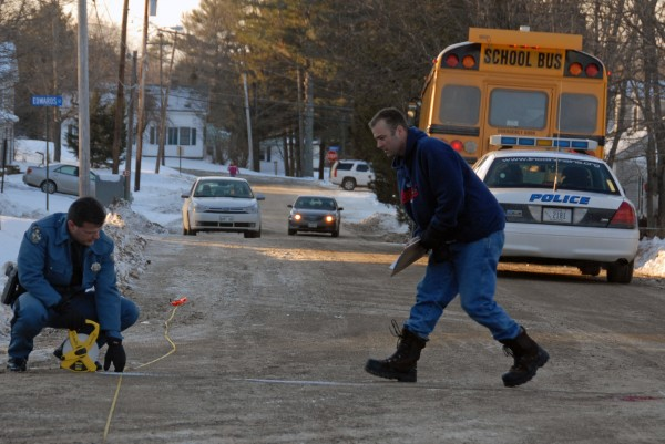 Maine State Police Trooper Thomas Fiske (left) and Trooper Larry Anderson take measurements at Ariel and Clark streets in Lincoln, where an unidentified girl was struck by a vehicle on Wednesday, Jan. 18, 2012.