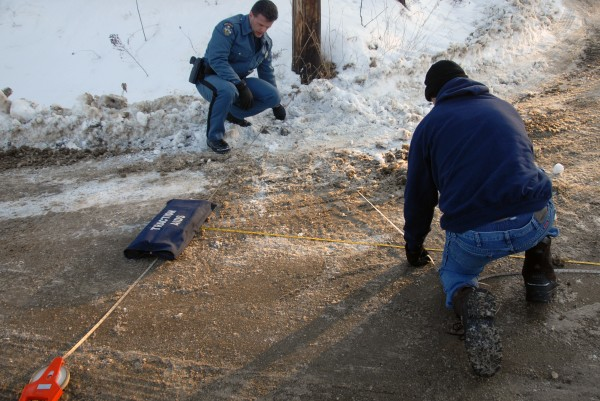 State police Trooper Thomas Fiske (left) and Trooper Larry Anderson take measurements at an accident scene at Ariel and Clark streets in Lincoln on Wednesday, Jan. 18, 2011. Police identified the victim the following day as Sophia Nelson, 6, of Lincoln.