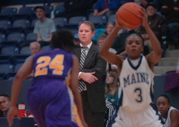 University of Maine women's coach Richard Barron (background) watches Brittany Williams (3) pass around University at Albany's Adrienne Jones (24) during Saturday's Big East  basketball game at Alfond Arena in Orono. The Great Danes outlasted the Lady Black Bears 60-48.