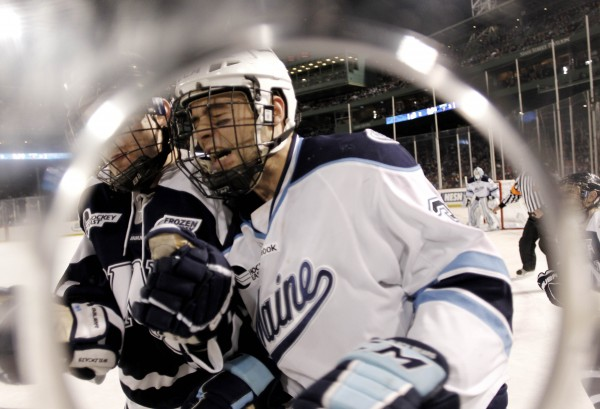 Maine's Mark Nemec (right) is checked by New Hampshire's Nick Sorkin during the second period of an NCAA college hockey game at Fenway Park in Boston, Saturday, Jan. 7, 2012.
