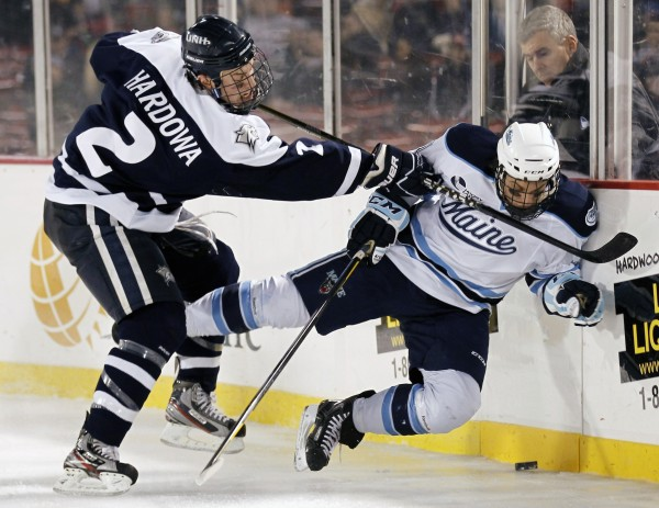 Maine's Theo Andersson, of Sweden, is checked by New Hampshire's Connor Hardowa (2) during the third period of Maine's 5-4 overtime win in an NCAA college hockey game at Fenway Park in Boston, Saturday, Jan. 7, 2012.