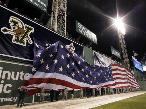 A United States flag is lowered from the Green Monster after the national anthem prior to an NCAA college hockey game between Maine and New Hampshire at Fenway Park in Boston, Saturday, Jan. 7, 2012.