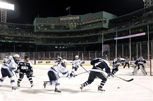 New Hampshire's Damon Kipp (4) tries to get away from Maine's Joey Diamond (39) during the first period of an NCAA college hockey game at Fenway Park in Boston, Saturday, Jan. 7, 2012.