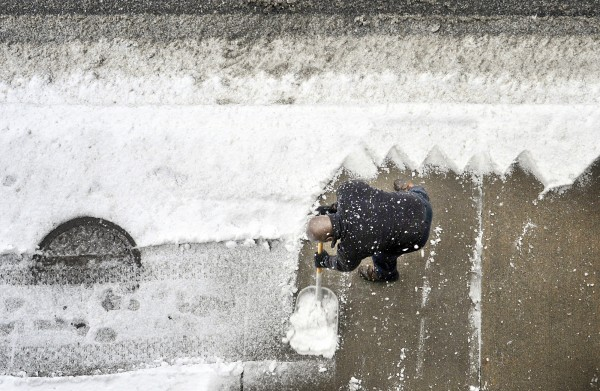 Marcus Scott, parking control supervisor for the City of Fitchburg, Mass., clears a sidewalk along on Boulder Drive in Fitchburg, Thursday Jan. 12, 2012, as the first snowstorm of the year passed through New England.