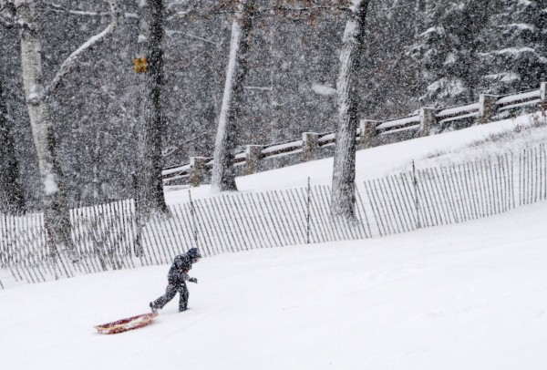 A boy hikes up the hill to go sledding during the first snowstorm of the winter, Thursday, Jan. 12, 2012 in Concord, N.H.