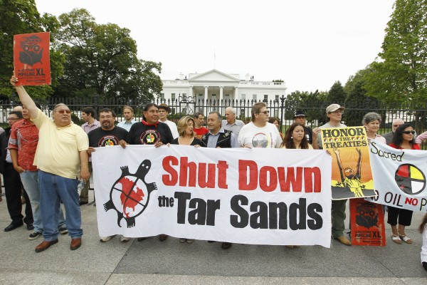 Demonstrators hold up signs in front of the White House in Washington in September to protest the Keystone XL Pipeline project in the U.S., and the Tar Sands Development in Alberta.