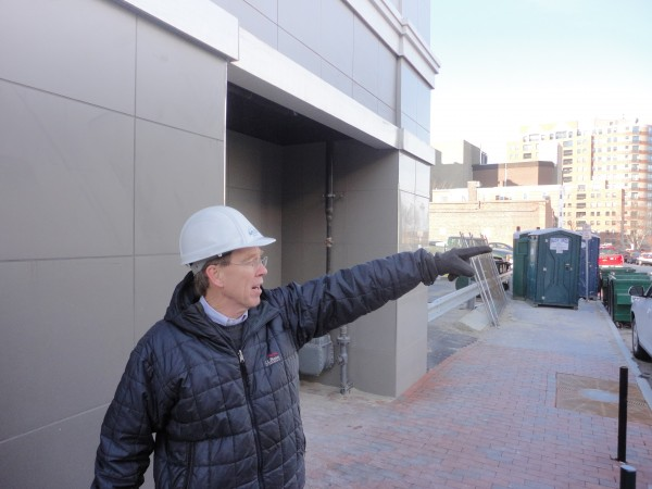 Dana Totman, president of Avesta Housing, points to apartment buildings along the skyline of Portland from the sidewalk alongside his organization's new Oak Street Lofts project. Oak Street Lofts is one of eight Avesta projects either recently finished, under construction or due to start soon.