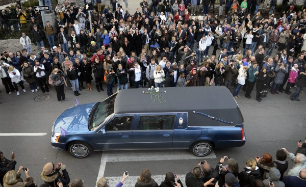 People pay their respects as the hearse carrying the casket of former Penn State football coach Joe Paterno passes through State College, Pa., Wednesday Jan. 25, 2012. Paterno died Sunday at the age of 85.