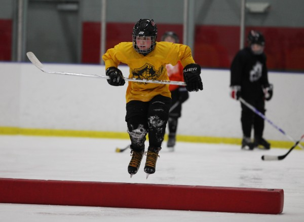 Portland Junior Pirates 2000AA player Jameson Bakke, jumps over an obstacle during practice Wednesday, Jan. 18, 2012 in Saco, Maine.