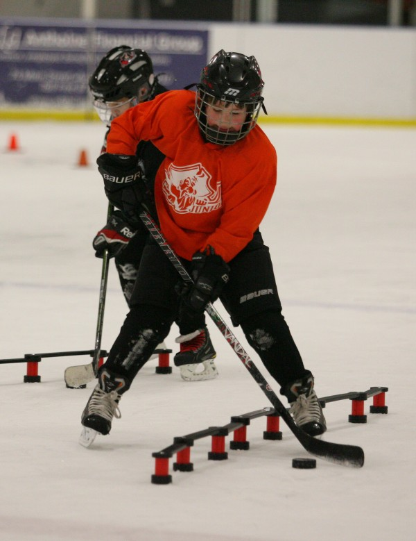 Portland Junior Pirates 2002AAA player Gabriel Older passes the puck through an obstacle during practice Wednesday, Jan. 18, 2012 in Saco, Maine.