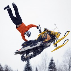 Seth Bell of Waterford, Maine, performs a seat grab heart attack in mid-air during a Rave-X freestyle show during the Snodeo, Saturday, Jan. 21, 2012, in Rangeley, Maine.
