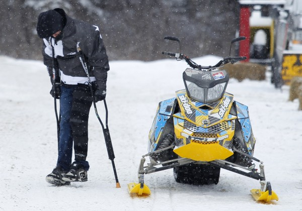 Joe McLafferty of Turner, Maine, hobbles by a snowmobile on crutches before a Rave-X freestyle show at the Snodeo, Saturday, Jan. 21, 2012, in Rangeley, Maine. McLafferty, one of the show's most accomplished performers, blew out his knee during a crash a couple days before the exhibition. After rehab, he plans to be back next year.