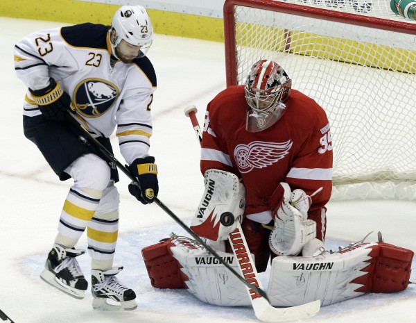 Detroit Red Wings goalie Jimmy Howard (35) stops a shot as Buffalo Sabres center Ville Leino (23), of Finland, tries for a rebound in the third period of an NHL hockey game in Detroit, Monday, Jan. 16, 2012.