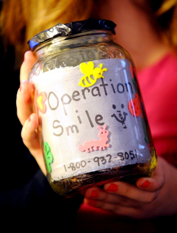 Molly McCormick, 12, of Turner shows a jar she uses to collect donations for Operation Smile. The international organization corrects facial deformities of young children. Molly has raised enough money for surgeries for eight children.