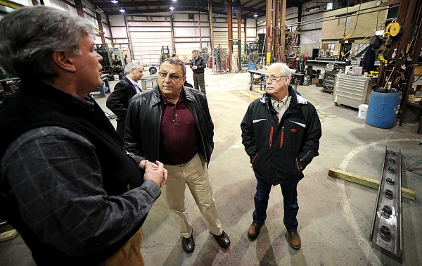 Gov. Paul LePage listens to Newfab Inc. owner and President Chip Roche (left) as he explains the products made at the Auburn metal fabricating facility during a &quotCapitol for a Day&quot tour Thursday. He was joined by Bruce Tisdale (right), president of Mountain Machine Works and Mountain Fluid Power.