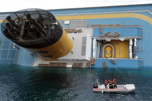 Italian firefighter scuba divers approach the cruise ship Costa Concordia leaning on its side, the day after it ran aground off the tiny Tuscan island of Giglio, Italy, Sunday, Jan. 15, 2012.
