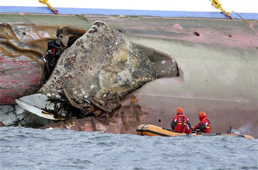 Firefighters on a dinghy look at a rock emerging from the side of the luxury cruise ship Costa Concordia, the day after it ran aground off the Tuscan island of Giglio, Italy, on Sunday, Jan. 15, 2012.