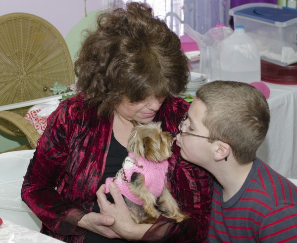 In this Jan. 7, 2012 photo provided by Howie Williams, Lucy, a mini Yorkshire terrier held by owner Sally Leone Montufar, receives a kiss from 11-year-old Sean Hebron, of Jackson, N.J.