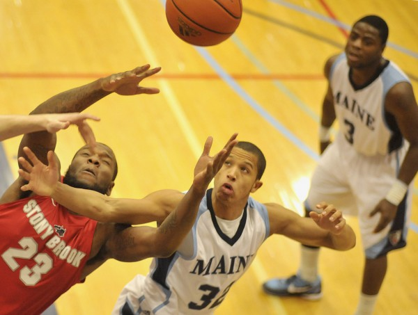 Stony Brook men's basketball player Dallis Joyner (23) and UMaine guard Gerald McLemore (32) both reach for a rebound  in the first half of their game in Orono on Saturday, Jan. 21, 2012.