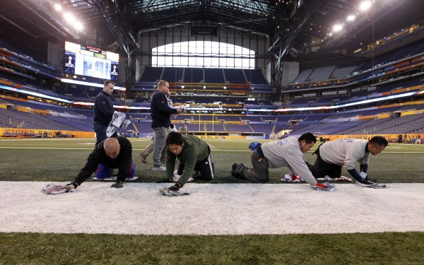 Members of the ground crew clean the field in Lucas Oil Stadium as preparations continue for Super Bowl XLVI in Indianapolis on Wednesday, Jan. 25, 2012. The New England Patriots are to face the New York Giants on Feb. 5.