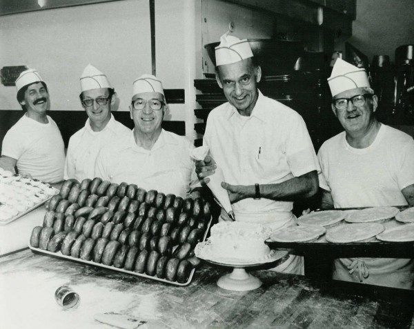 Walter Beaulieu, Ben Gunn, Joseph Soucy, Frank Soucy, and Dwight Frasier pose with a pan of raised glazed doughnuts, cake and turkey pies in 1985.