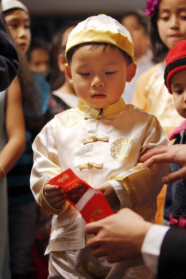Kevin Tran, 3, recieves a lucky money envelope during a celebration of the Vietnamese Lunar New Year, Saturday, Jan. 14, in Portland. Asian cultures traditionally give lucky money envelopes to the young and the old during the holiday.