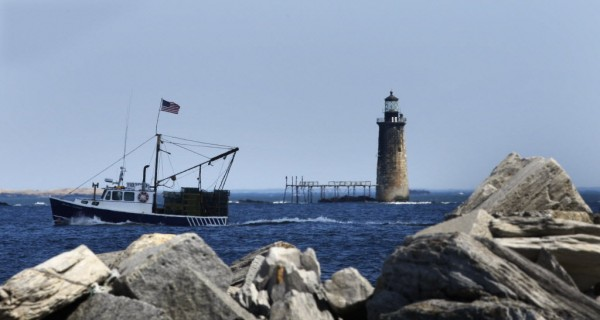 In this April 2009 file photo, a commercial fishing boat passes Ram Island Ledge Light, near Cape Elizabeth, Maine, on its way back to Portland Harbor. (AP Photo/Robert F. Bukaty)