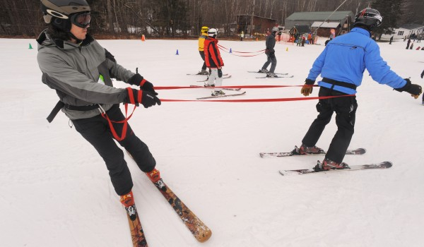 Matt Jorgensen (left) guides Bruce Kapp with the aid of a tether while training at the Camden Snow Bowl Saturday.
