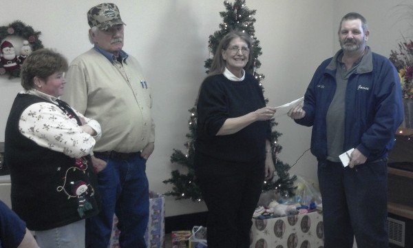 Kathy Scott of the Bluegrass Music Association of Maine board of directors, association vice president George Scott and association president Deb Burdin present a $200 donation from the association to James Macomber of the Piscataquis Santa Fund.