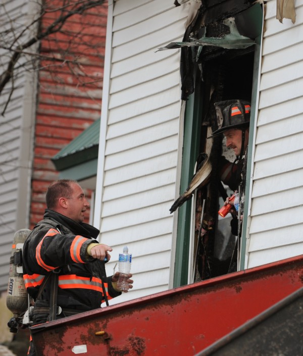 Brewer firefighters confer at 27 High Street in Brewer on Jan. 24, 2012, after responding to reports of a smoke-filled home.